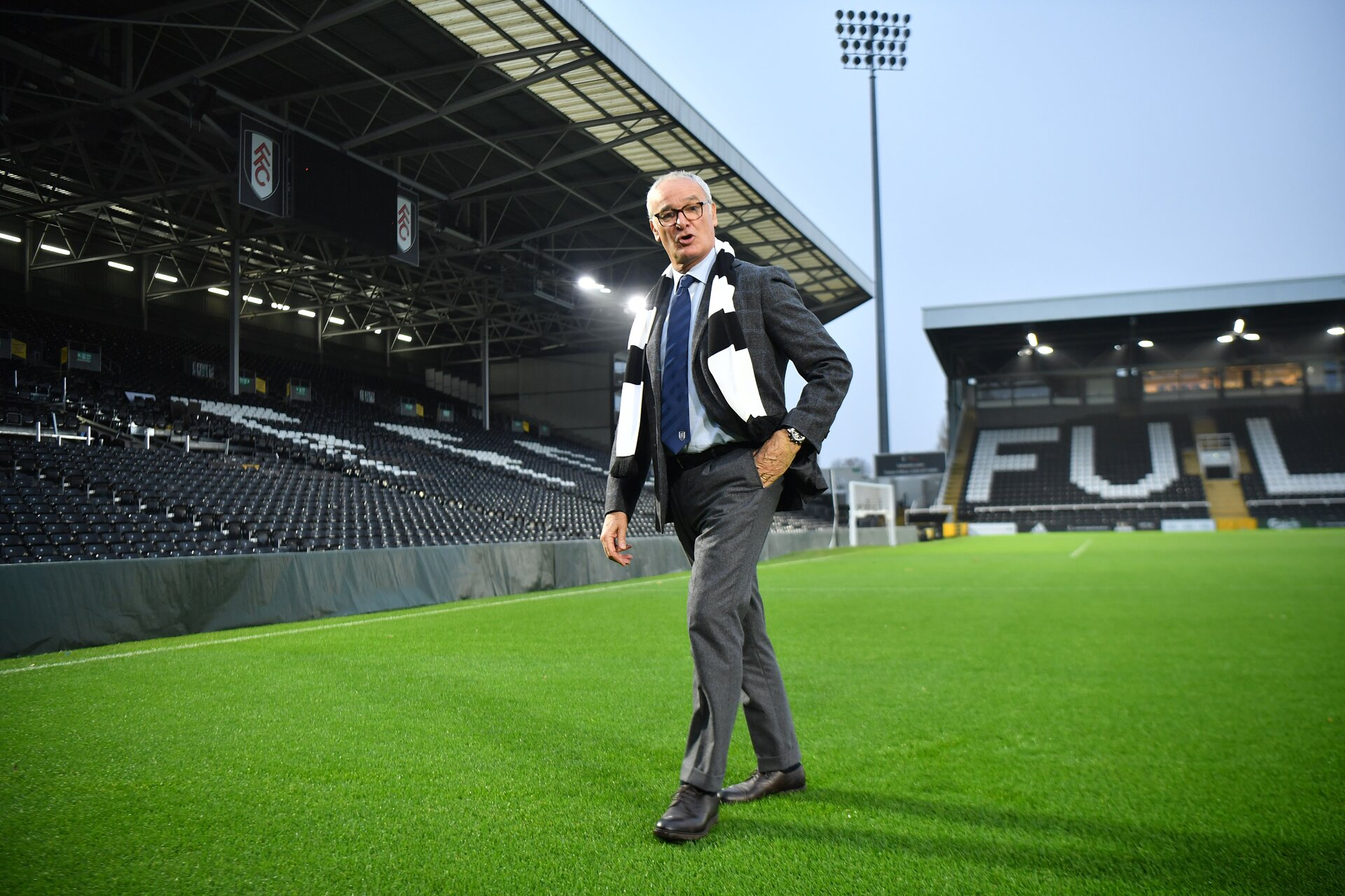 Fulham's new Italian manager Claudio Ranieri poses with a team scarf on the pitch at the club's Craven Cottage stadium on November 16, 2018. (Photo by BEN STANSALL / AFP) / RESTRICTED TO EDITORIAL USE. No use with unauthorized audio, video, data, fixture lists, club/league logos or 'live' services. Online in-match use limited to 75 images, no video emulation. No use in betting, games or single club/league/player publications. /         (Photo credit should read BEN STANSALL/AFP/Getty Images)