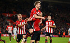 SOUTHAMPTON, ENGLAND - JANUARY 16: Stuart Armstrong (middle) of Southampton FC scores and celebrates by jumping on his team mate Shane Long during the FA Cup Third Round Replay match between Southampton FC and Derby County at St Mary's Stadium on January 16, 2019 in Southampton, United Kingdom. (Photo by James Bridle - Southampton FC/Southampton FC via Getty Images)