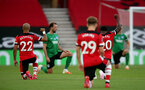 SOUTHAMPTON, ENGLAND - JULY 16: Nathan Redmond (L) and Michael Obafemi (R) of southampton taking a knee in support of the Black Lives Matter movement ahead of the Premier League match between Southampton FC and Brighton & Hove Albion at St Mary's Stadium on July 16, 2020 in Southampton, United Kingdom. Football Stadiums around Europe remain empty due to the Coronavirus Pandemic as Government social distancing laws prohibit fans inside venues resulting in all fixtures being played behind closed doors. (Photo by Chris Moorhouse/Southampton FC via Getty Images)