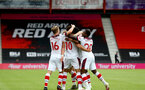BOURNEMOUTH, ENGLAND - JULY 19: Ché Adams surrounded by team mates celebrating his late goal during the Premier League match between AFC Bournemouth and Southampton FC at Vitality Stadium on July 19, 2020 in Bournemouth, United Kingdom. Football Stadiums around Europe remain empty due to the Coronavirus Pandemic as Government social distancing laws prohibit fans inside venues resulting in all fixtures being played behind closed doors. (Photo by Matt Watson/Southampton FC via Getty Images)