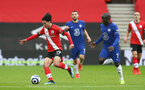 SOUTHAMPTON, ENGLAND - FEBRUARY 20: Takumi Minamino(L) of Southampton and N'Golo Kante (R) of Chelsea during the Premier League match between Southampton and Chelsea at St Mary's Stadium on February 20, 2021 in Southampton, England. Sporting stadiums around the UK remain under strict restrictions due to the Coronavirus Pandemic as Government social distancing laws prohibit fans inside venues resulting in games being played behind closed doors. (Photo by Matt Watson/Southampton FC via Getty Images)