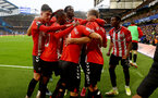 LONDON, ENGLAND - OCTOBER 02: James Ward-Prowse of Southampton is mobbed by his team mates after scoring during the Premier League match between Chelsea and Southampton at Stamford Bridge on October 02, 2021 in London, England. (Photo by Matt Watson/Southampton FC via Getty Images)